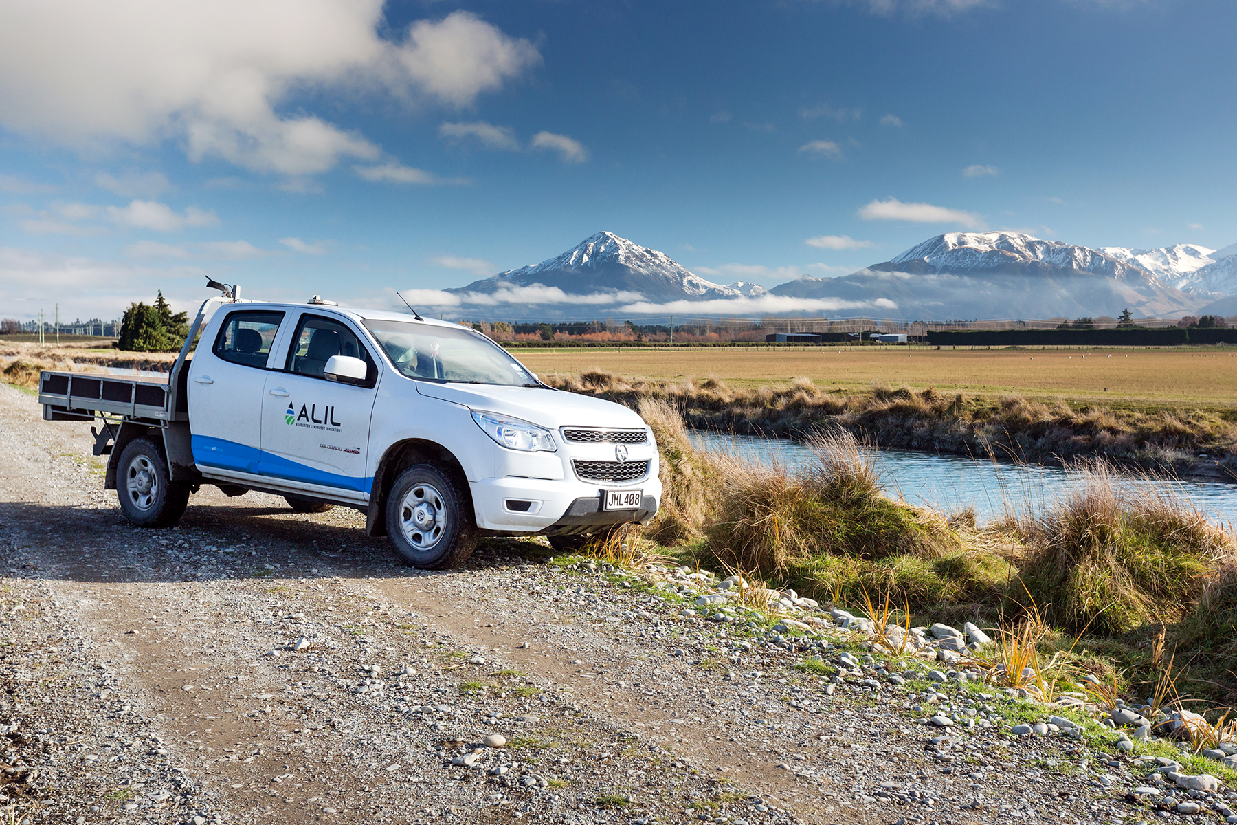 ALIL ute parked by a stream with mountains in the background - Ashburton Lyndhurst Irrigation Limited